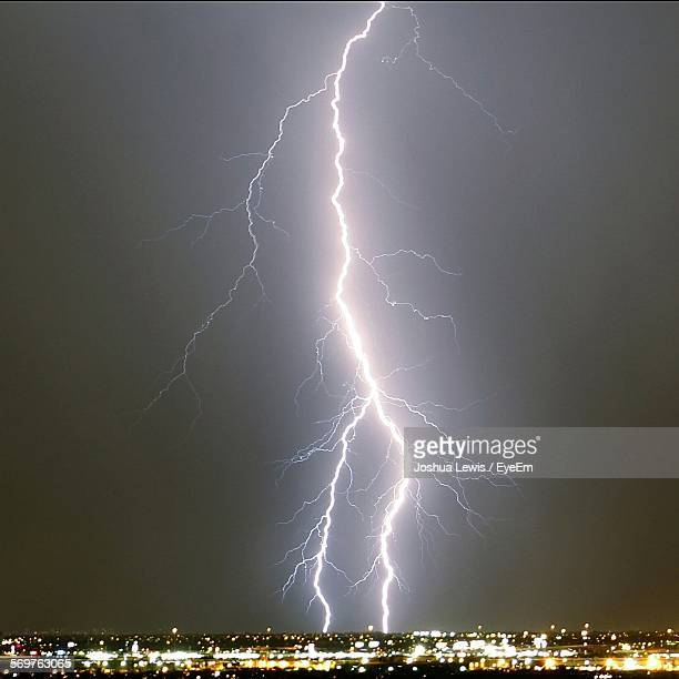 Idyllic Shot Of Thunder Lightning Over Illuminated Cityscape