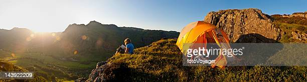 Idyllic summer camping child reading in mountains