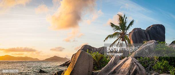 Idyllic tropical island sunset over palm tree beach ocean lagoon