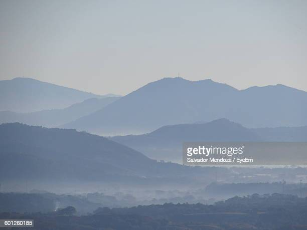 Idyllic View Of Landscape Against Sky During Foggy Weather
