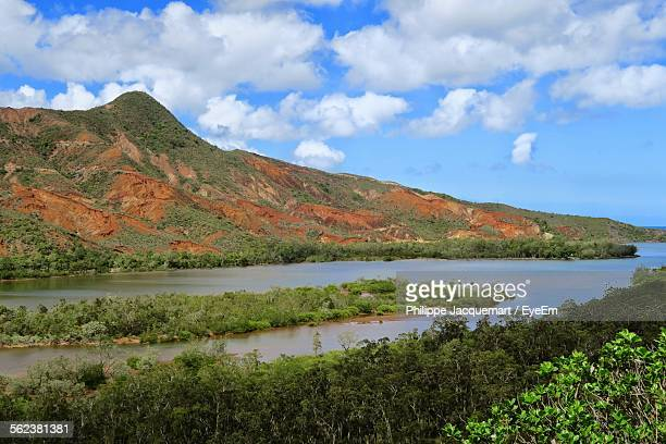 Idyllic View Of Mountain And River Against Cloudy Sky