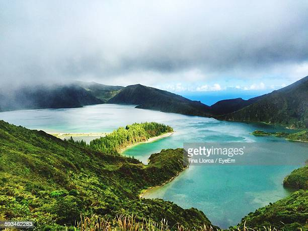 Idyllic View Of Mountains And River Against Cloudy Sky