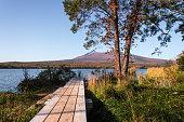 Idyllic view of a boardwalk in front of Mount Komagatake, Lake Onuma, Onuma Quasi National Park, Hokkaido, Japan. Autumn 2016