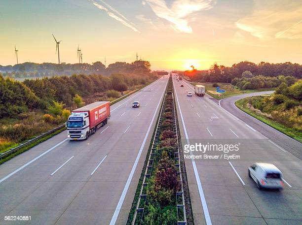 Idyllic View Of Multiple Lane Highway By Wind Turbine Field