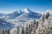 Beautiful winter wonderland mountain landscape in the Bavarian Alps with village of Berchtesgaden and Watzmann mountain summit in the background at sunrise, Nationalpark Berchtesgadener Land, Bavaria,