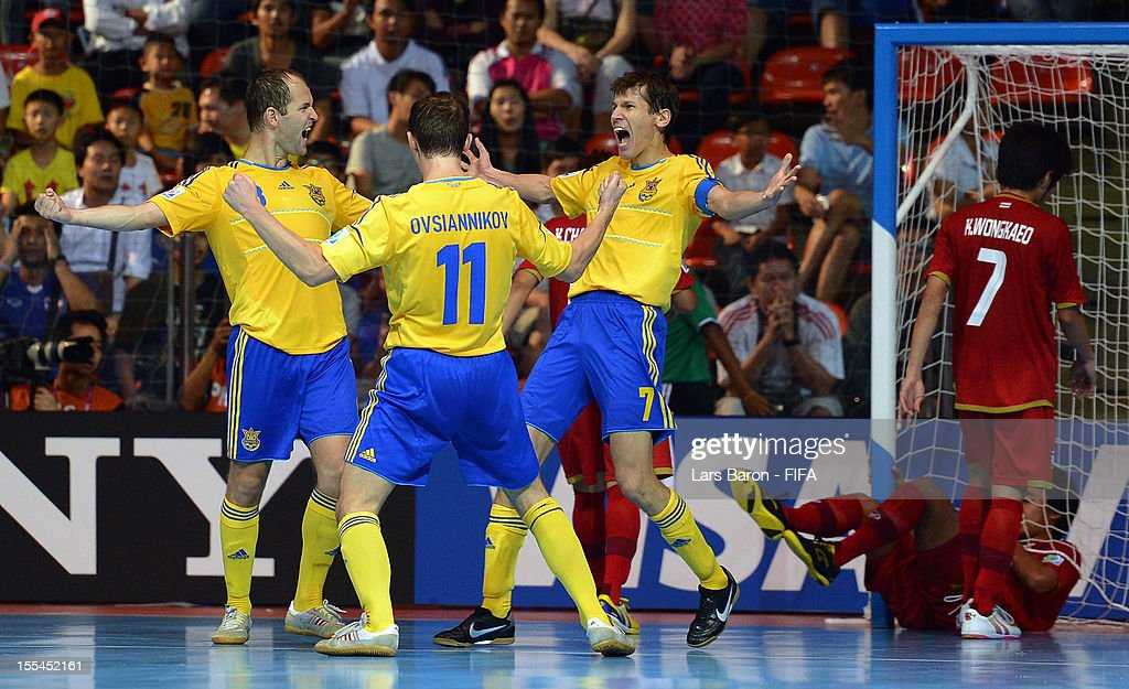 Ievgen Rogachov of Ukraine celebrates with team mates Denys Ovsiannikov and Maksym Pavlenko during the FIFA Futsal World Cup Group A match between Thailand and Ukraine at Indoor Stadium Huamark on November 4, 2012 in Bangkok, Thailand.