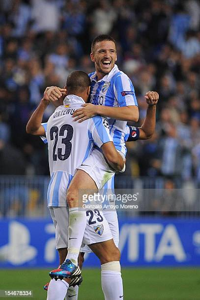 Ignacio Camacho of Malaga CF celebrates victory with teammate Oguchi Onyewu after the UEFA Champions League group C match between Malaga CF and AC...