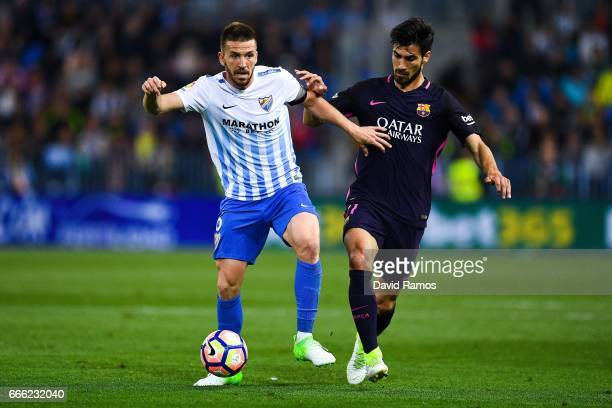 Ignacio Camacho of Malaga CF competes for the ball with Andre Gomes of FC Barcelona during the La Liga match between Malaga CF and FC Barcelona at La...