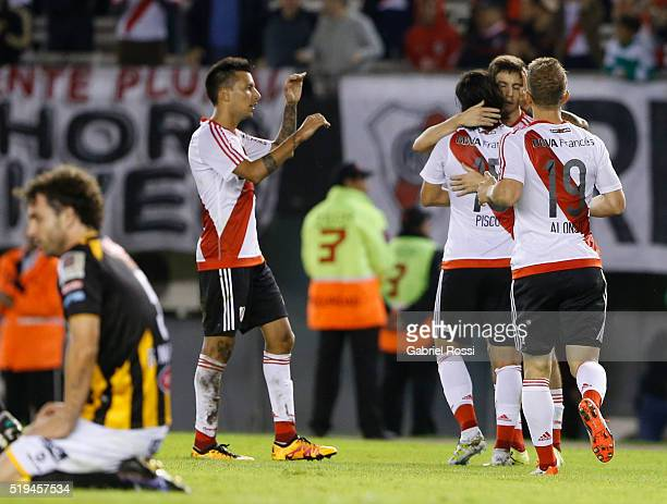 Ignacio Fernandez of River Plate celebrates with teammates Leonardo Pisculichi and Ivan Alonso after scoring the sixth goal of his team during a...