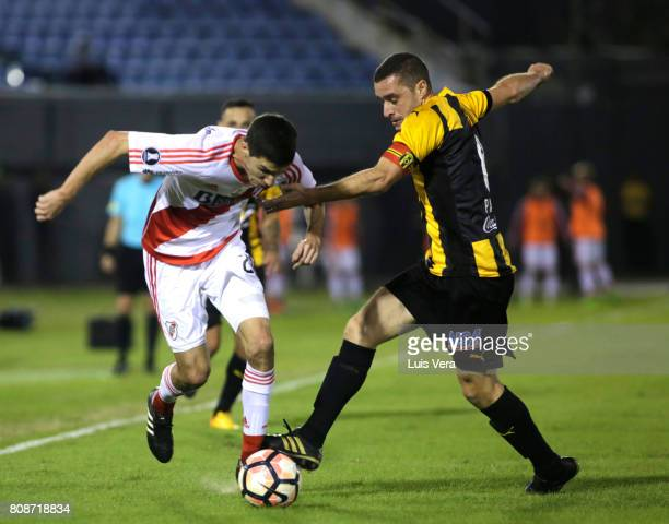 Ignacio Fernandez of River Plate fights for the ball with Marcelo Palau of Guarani during a first leg match between Guarani and River Plate as part...