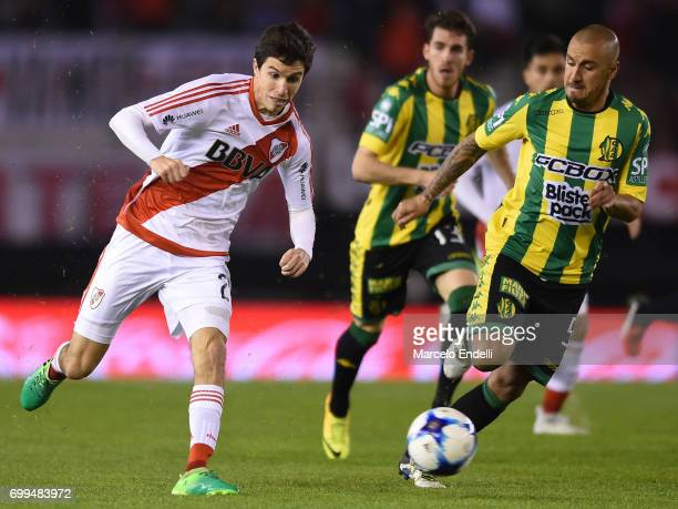 Ignacio Fernandez of River Plate plays the ball followed by Roberto Brum of Aldosivi during a match between River Plate and Aldosivi as part of...