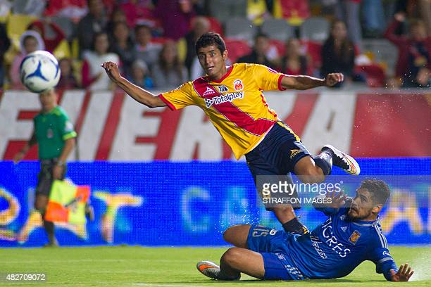 Ignacio Gonzalez of Monarcas shoots over Manuel Viniegra of Tigres during a 2nd round match between Morelia and Tigres UANL as part of the Apertura...