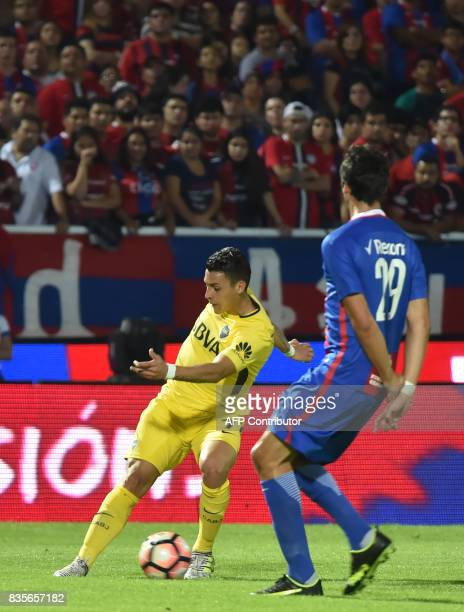 Ignacio Pallas of Paraguays Cerro Porteno vies for the ball with Cristian Pavon of Argentina's Boca Juniors during a friendly match at the...