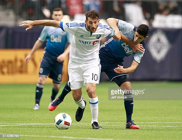 Ignacio Piatti of the Montreal Impact holds off Matias Laba of the Vancouver Whitecaps and he dribbles the ball upfield during their MLS game March 6...