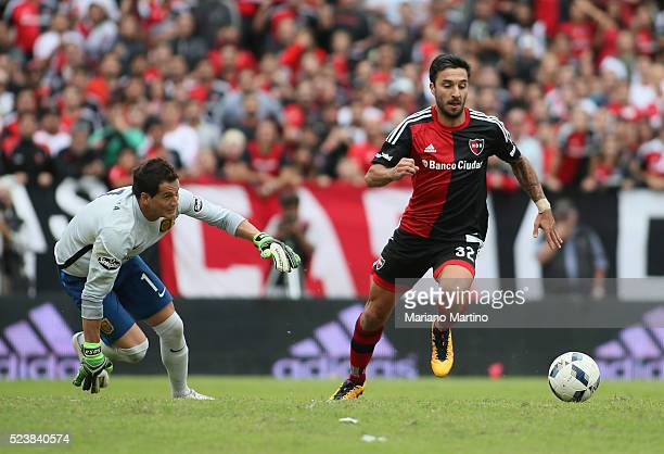Ignacio Scocco of Newells dribbles past Sebastian Sosa goalkeeper of Central during a match between Newell's Old Boys and Rosario Central as part of...