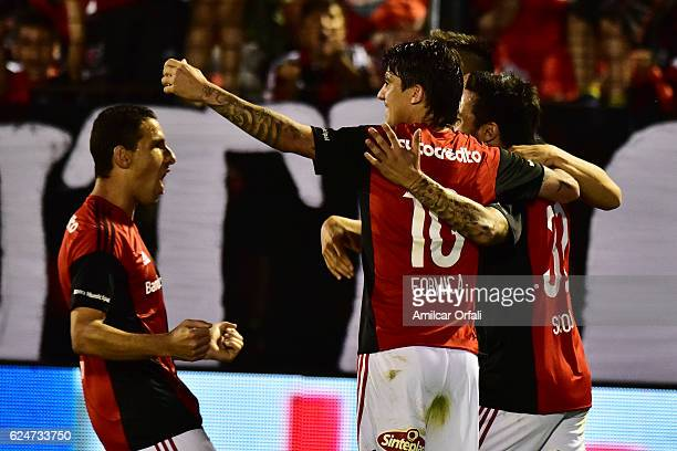 Ignacio Scocco of Newells Old Boys celebrates with teammates Mauro Formica and Maximiliano Rodriguez after scoring the first goal of his team during...