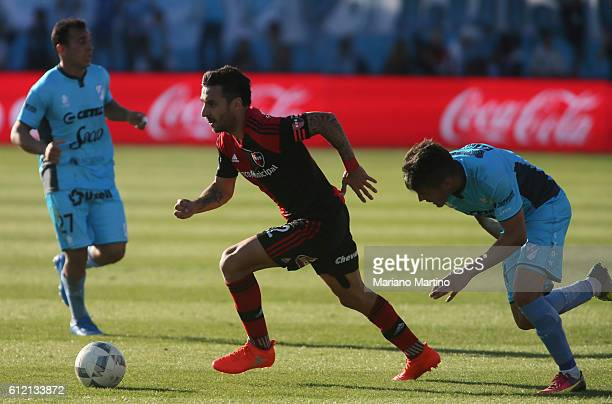 Ignacio Scocco of Newell's Old Boys drives the ball between Gonzalo Escobar and Lucas Mancinelli of Temperley during a match between Temperley and...