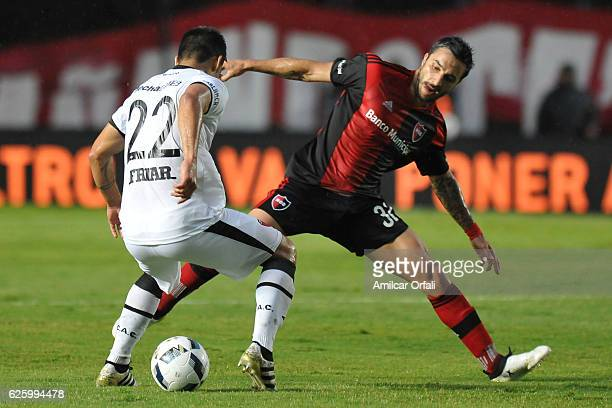 Ignacio Scocco of Newell´s Old Boys struggles for the ball with Ivan Torres of Colon during a match between Colon and Newell's Old Boys as part of...