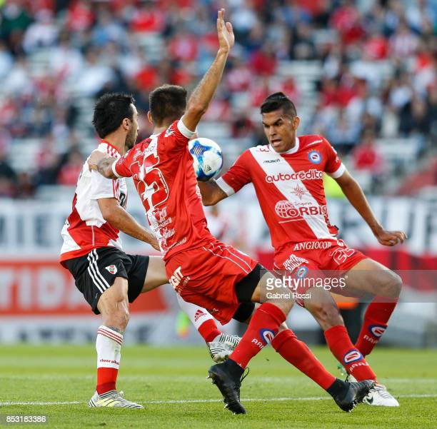 Ignacio Scocco of River Plate fights for the ball with Juan Saiz of Argentinos Juniors during a match between River Plate and Argentinos Juniors as...