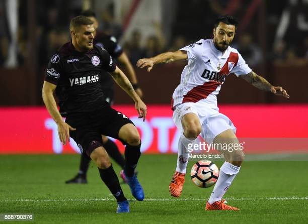 Ignacio Scocco of River Plate fights for the ball with Nicolas Pasquini of Lanus during a second leg match between Lanus and River Plate as part of...
