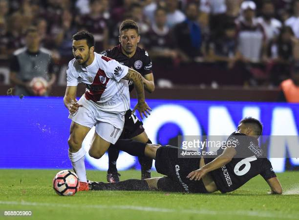 Ignacio Scocco of River Plate fights for the ball with Rolando Garcia and Diego Braghieri of Lanus during a second leg match between Lanus and River...