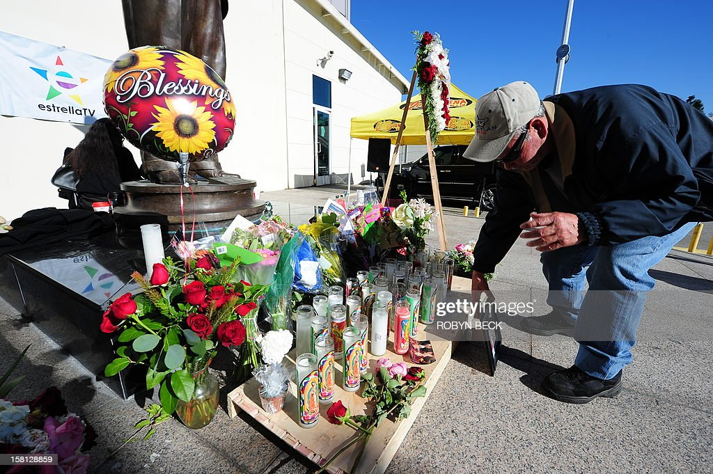 Ignancio Sanchez places a photograph at a memorial of flowers, candles, ballons and notes to the late Mexican-American singing superstar Jenni Rivera, December 10, 2012 in Burbank, California. Rescue workers searched Monday the wreckage of a plane that carried Rivera, a star on both sides of the border, whose death shocked Latin music fans and celebrities. AFP PHOTO/ROBYN BECK