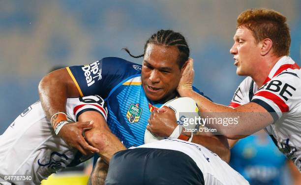 Ignattius Paasi of the Titans is tackled during the round one NRL match between the Gold Coast Titans and the Sydney Roosters at Cbus Super Stadium...