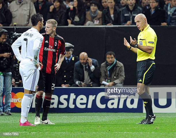Ignazio Abate of Milan and Cristiano Ronaldo of Real Madrid are summoned by referee Howard Webb during the Uefa Champions League group G match...