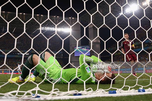 Igor Akinfeev of Russia lies in the net after failing to save a shot by Lee KeunHo of South Korea for South Korea's first goal during the 2014 FIFA...