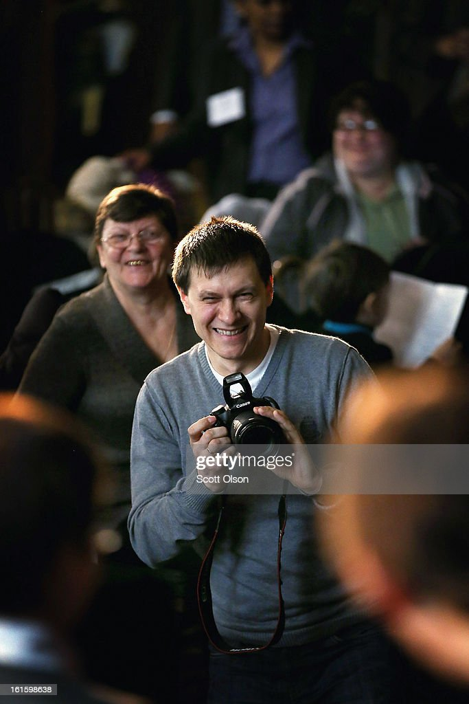 Igor Bugaian, who is from Moldova, takes a picture as his nine-year-old son Christian receives a citizenship certificate during a ceremony at the Chicago Cultural Center on February 12, 2013 in Chicago, Illinois. The ceremony was held to recognize as new U.S. citizens 62 children, ages 6-18, from 23 countries who were adopted from abroad or who derived U.S. citizenship when their immigrant parents were naturalized.