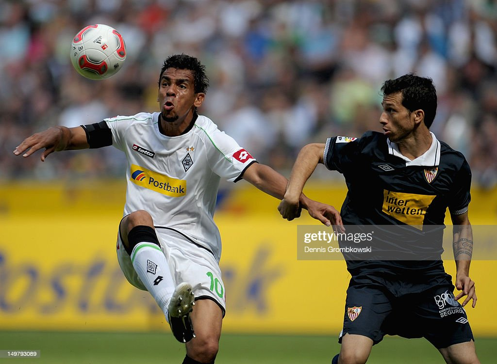 <a gi-track='captionPersonalityLinkClicked' href=/galleries/search?phrase=Igor+de+Camargo&family=editorial&specificpeople=2514599 ng-click='$event.stopPropagation()'>Igor de Camargo</a> of Moenchengladbach and <a gi-track='captionPersonalityLinkClicked' href=/galleries/search?phrase=Cicinho&family=editorial&specificpeople=243232 ng-click='$event.stopPropagation()'>Cicinho</a> of Sevilla battle for the ball during the friendly match between Borussia Moenchengladbach and FC Sevilla at Borussia-Park on August 4, 2012 in Moenchengladbach, Germany.