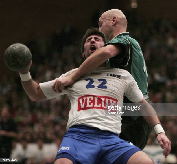 Igor Lavrov of Hamburg is attacked by Robertas Pauzuolis of Hannover Burgdorf during the German Handball Cup match between Hannover Burgdorf and HSV...