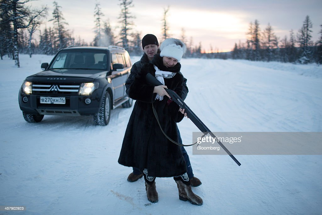 Igor Tazarachev, an OAO Alrosa mining engineer, teaches his wife to shoot in the taiga forest outside the mining town of Udachny, Sakha Republic, Russia, on Monday, Dec. 16, 2013. Russia plans to maintain control of Mirny-based Alrosa, which produces a quarter of the world's diamonds by value and more rough diamonds than De Beers by carat. Photographer: Andrey Rudakov/Bloomberg via Getty Images