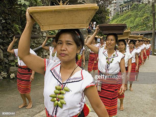 Igorot tribeswomen parade barefoot carrying baskets of freshly harvested native rice on April 15 2008 during the traditional threeday Imbayah...