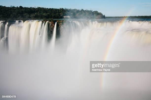 Iguazu Falls, Argentina: A rainbow appears through mist at waterfall edge