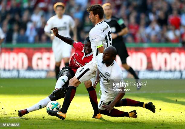 Ihlas Bebou of Hannover and David Abraham and Jetro Willems of Frankfurt battle for the ball during the Bundesliga match between Hannover 96 and...