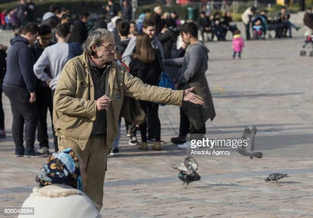 Ihsan Adnan Ercan 60yearold Turkish man who has been staying at 'Yeni Sukran Hotel' for 25 years feeds pigeons at Konak Square in Izmir Turkey on...