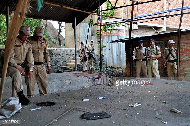 iIndian security personel check the site of a bomb blast at Singjamei Chingamakhong in Imphal in northeastern Manipur state on May 29 2014 A powerful...