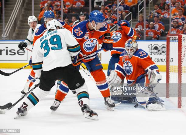 Iiro Pakarinen and goalie Cam Talbot of the Edmonton Oilers protect the net against Logan Couture of the San Jose Sharks in Game One of the Western...
