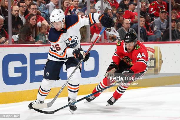 Iiro Pakarinen of the Edmonton Oilers and Jan Rutta of the Chicago Blackhawks chase the puck in the first period at the United Center on October 19...