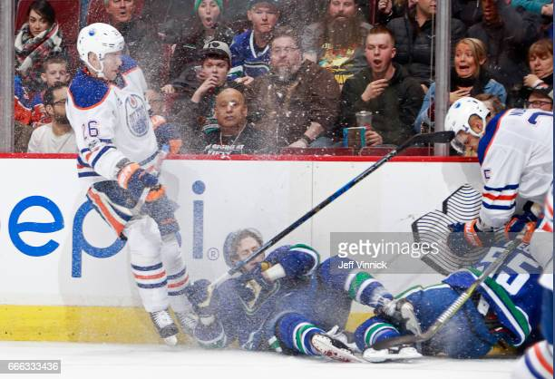 Iiro Pakarinen of the Edmonton Oilers gets a penalty for interference after checking over Griffen Molino of the Vancouver Canucks during their NHL...
