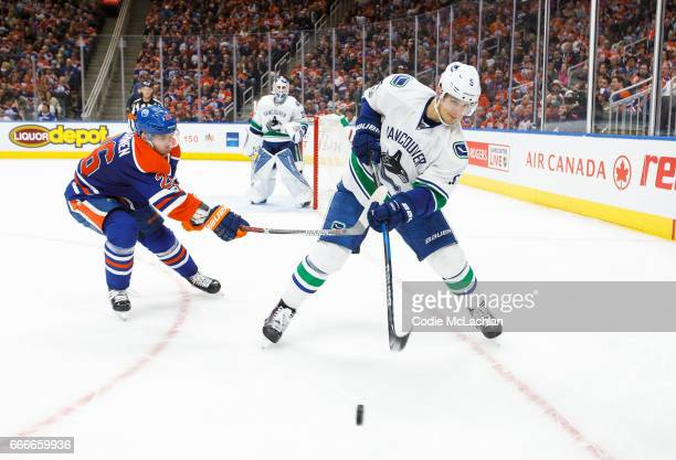 Iiro Pakarinen of the Edmonton Oilers hassles Luca Sbisa of the Vancouver Canucks on April 9 2017 at Rogers Place in Edmonton Alberta Canada