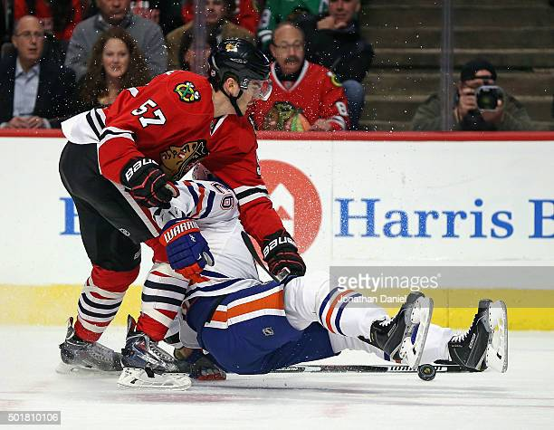 Iiro Pakarinen of the Edmonton Oilers is smothered by Trevor van Riemsdyk of the Chicago Blackhawks at the United Center on December 17 2015 in...