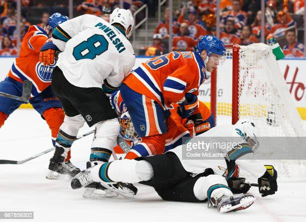 Iiro Pakarinen of the Edmonton Oilers takes Logan Couture of the San Jose Sharks to the ice in Game One of the Western Conference First Round during...