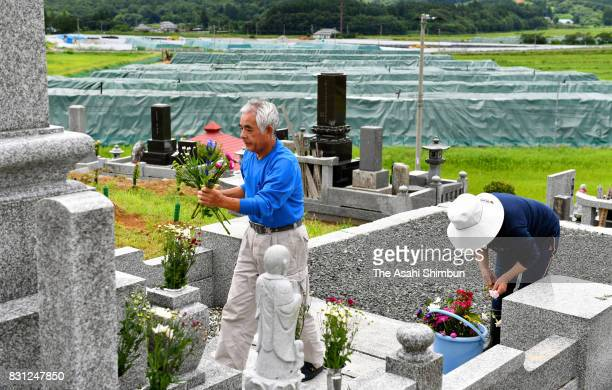Iitate Village residents visit their family grave while a temporary storage site for radioactive waste generated from decontamination work is seen in...