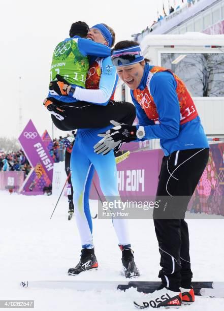 Iivo Niskanen of Finland celebrates with compatriots AinoKaisa Saarinen and Kerttu Niskanen of Finland after winning the gold medal with teammate...