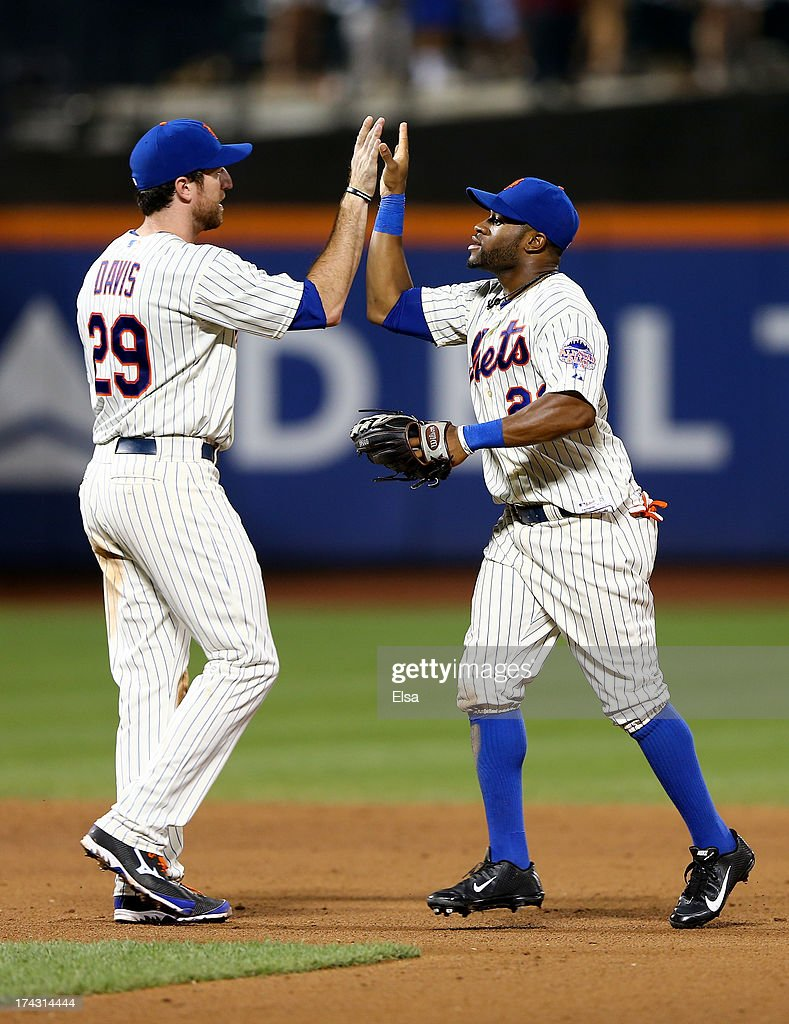 Ike Davis #29 and Eric Young Jr. #22 of the New York Mets celebrate the win over the Atlanta Braves on July 23, 2013 at Citi Field in the Flushing neighborhood of the Queens borough of New York City. The New York Mets defeated the Atlanta Braves 4-1.