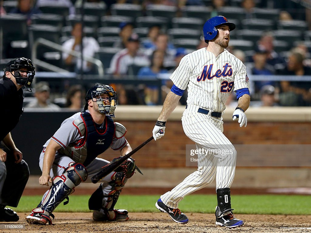 Ike Davis #29 of the New York Mets hits an RBI double as Brian McCann #16 of the Atlanta Braves defends on July 23, 2013 at Citi Field in the Flushing neighborhood of the Queens borough of New York City.
