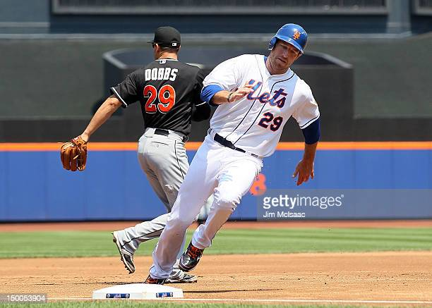 Ike Davis of the New York Mets rounds third base to score a second inning run past Greg Dobbs of the Miami Marlins at Citi Field on August 9 2012 in...