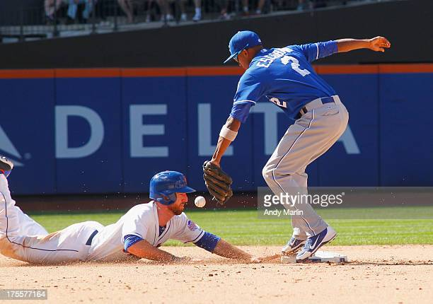 Ike Davis of the New York Mets slides back into second base ahead of the tag from Alcides Escobar of the Kansas City Royals to avoid a double play in...